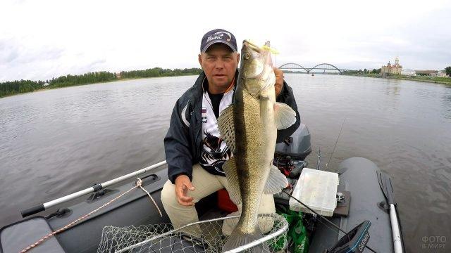 Рыбак демонстрирует улов сидя в лодке посреди Волги