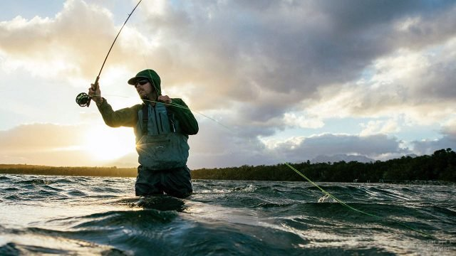 Рыбак со спиннингом стоит по пояс в воде на фоне утреннего неба над рекой