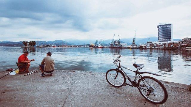 Рыбаки и велосипед на берегу залива в европейском портовом городе