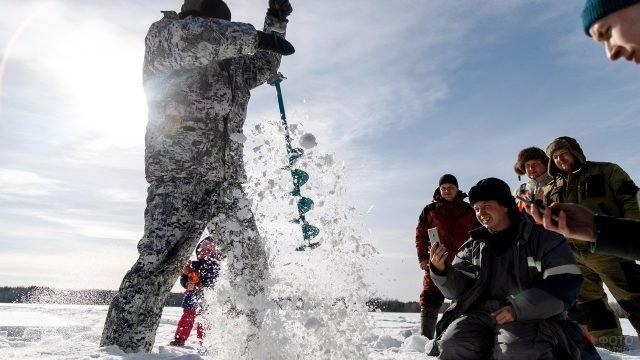 Рыбаки снимают на смартфоны товарища с ледобуром
