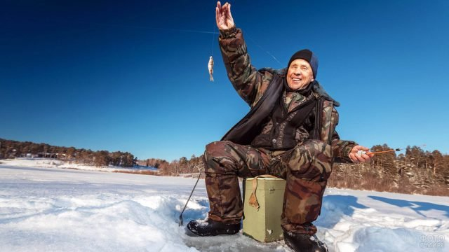 Счастливый пенсионер с рыбкой над лункой на зимней Волге
