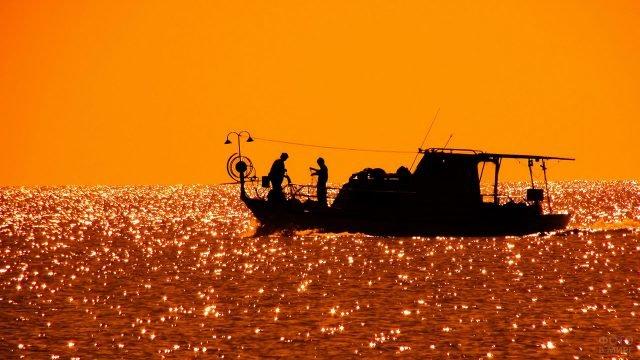 Силуэт рыбацкого катера с двумя рыболовами на фоне заката над морем