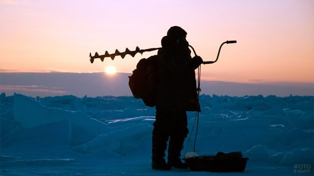 Силуэт рыбака с ледобуром на плече на берегу зимнего Каспия