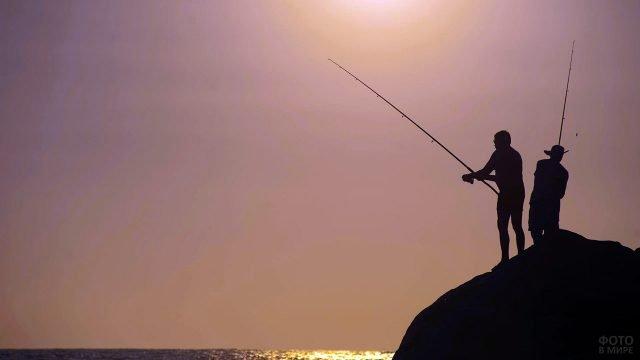 Силуэты двух туристов, рыбачащих с прибрежной скалы на фоне заката над морем