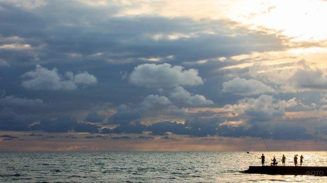 Туристы ранним утром ловят рыбу с волнореза на фоне облаков над морем