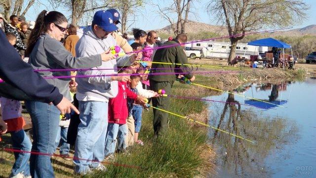 Туристы с детьми учатся ловить рыбу на берегу горного озера