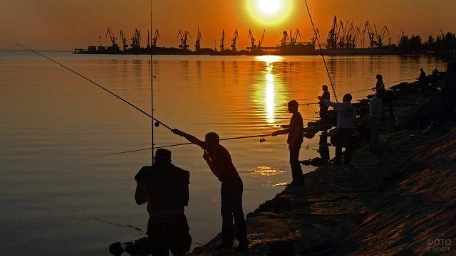 Утренняя рыбалка с берега в Азовском море - силуэты рыбаков и портовых кранов