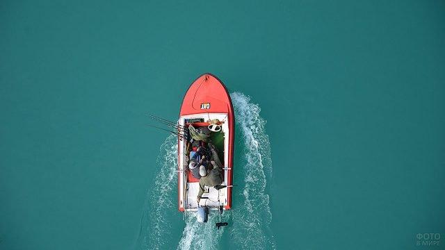 Вид сверху на рыбаков в красной моторной лодке посреди бирюзовой водной глади