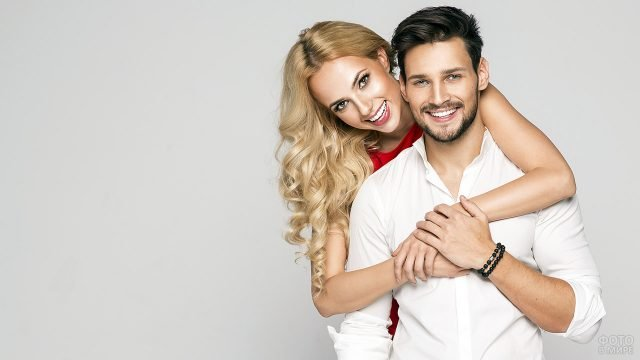 Блондинка в красном обнимает за плечи юношу в белой рубашке
