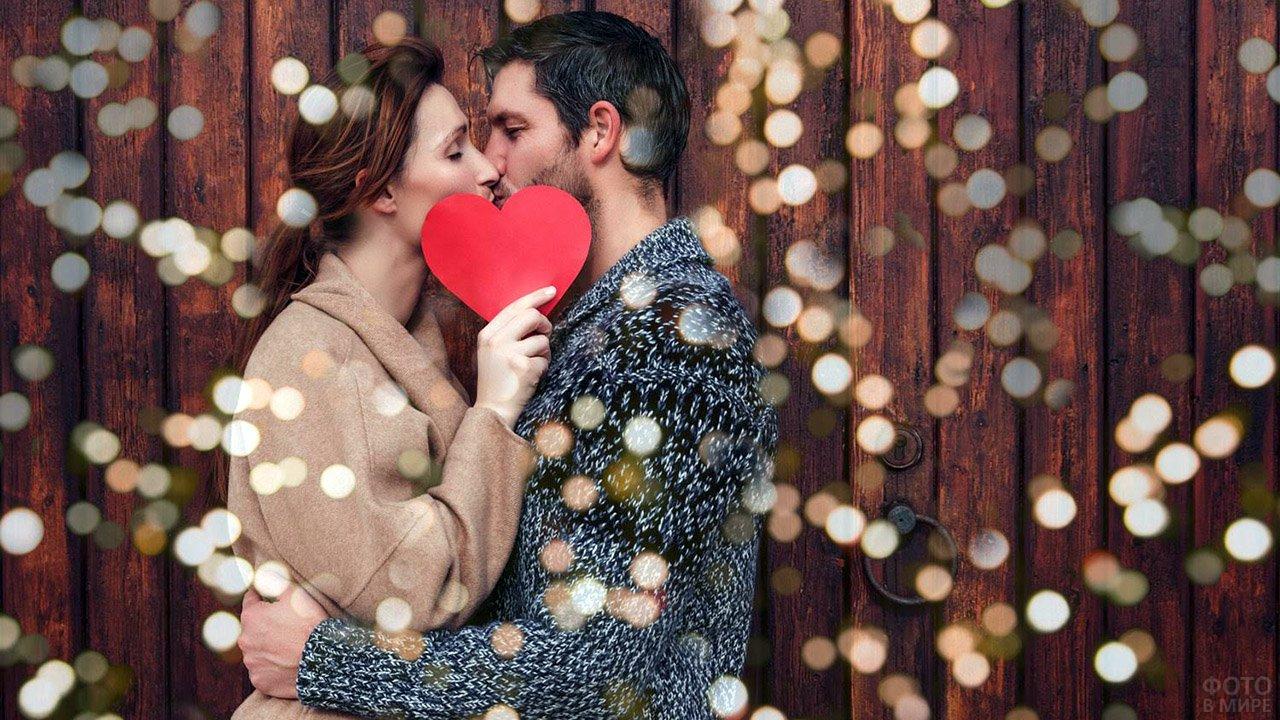Целующиеся влюблённые с сердечком-валентинкой в руках среди огоньков-бокэ