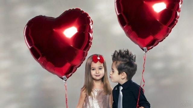 Дети позируют на День влюблённых с воздушными шарами-сердечками
