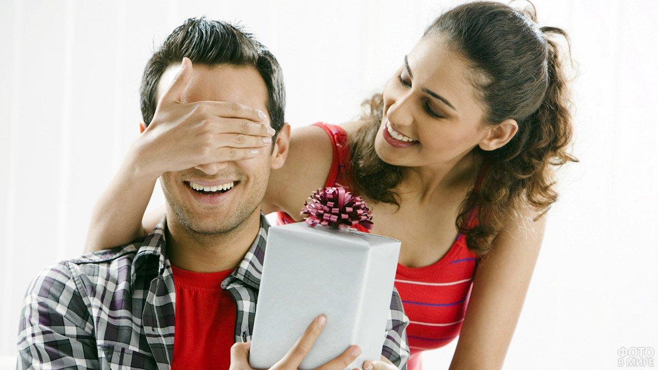 Девушка закрыла ладонью глаза любимому, протягивающему подарок