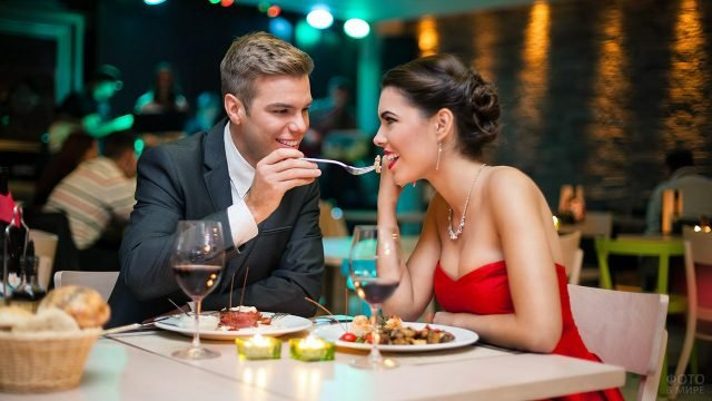 Юноша кормит смеющуюся девушку в красном на романтичном ужине в ресторане