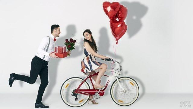 Юноша с подарками и девушка на велосипеде с шариками-сердечками позируют в фотостудии