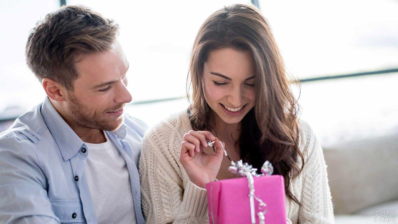 Юноша смотрит на девушку, распаковывающую подарок