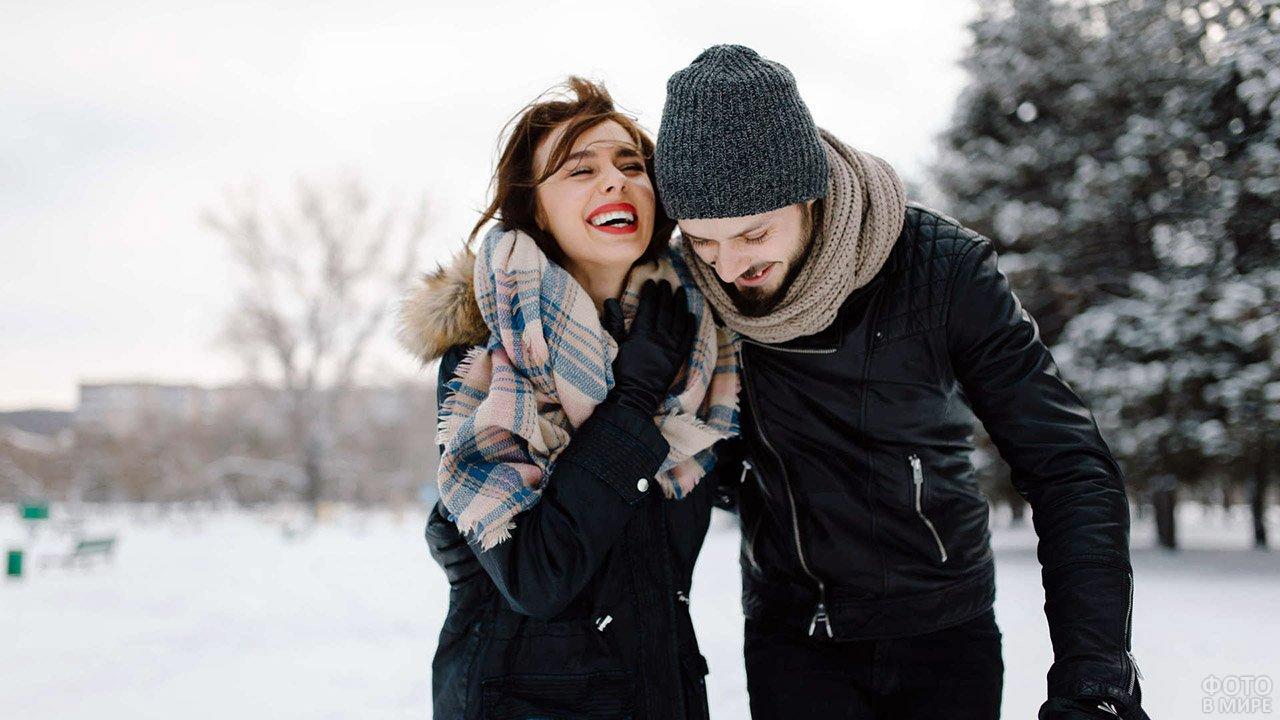 Молодая парочка смеясь гуляет в зимнем парке