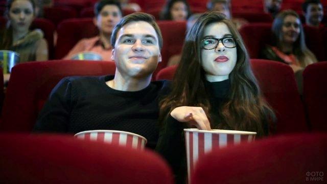 Молодёжь с попкорном на свидании в кинозале