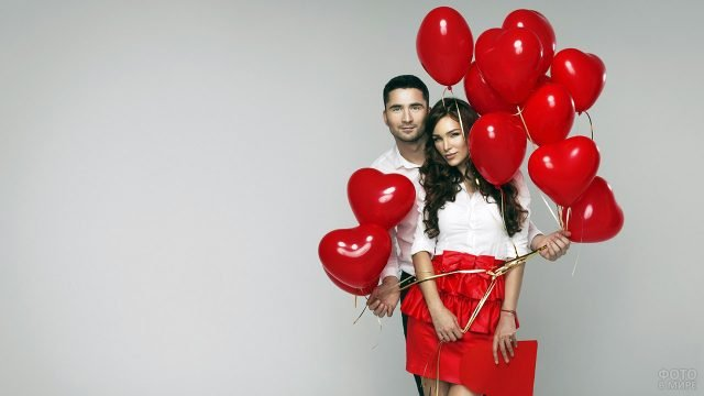 Нарядная парочка позирует с валентинкой и воздушными шариками-сердечками