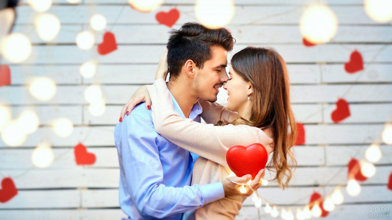 Обнимающаяся пара среди гирлянд с сердечками