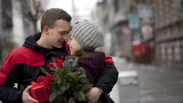 Обнимающаяся парочка с подарками на День влюблённых под снегопадом