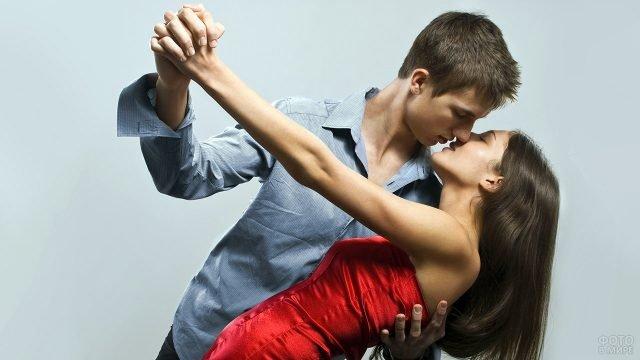 Пара целуется в танце, позируя в фотостудии