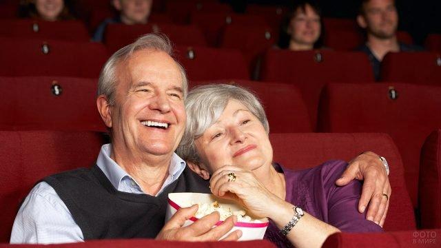 Пара пенсионеров сидят в обнимку и смотрят фильм в кинотеатре