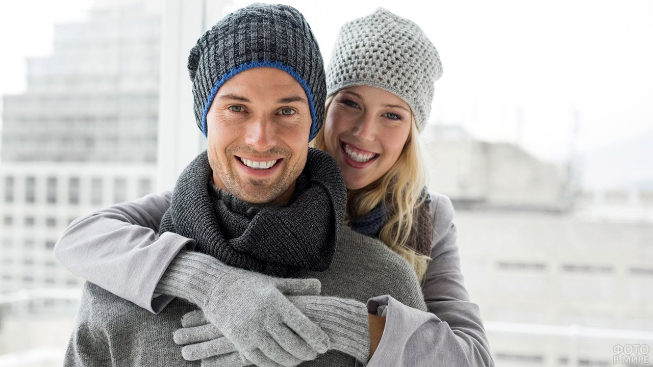 Пара в вязанных шапках позирует на фоне зимнего города