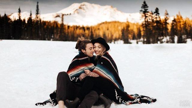 Парочка хипстеров сидят на снегу завернувшись в плед