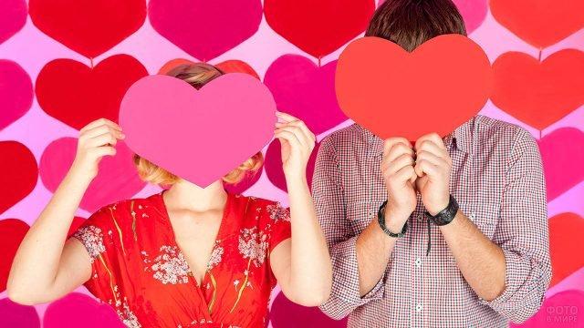 Парочка на фоне сердечек позирует пряча лица за сердечками