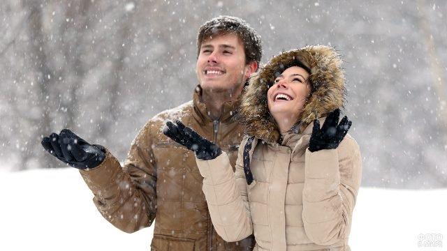 Парочка под снегопадом в зимнем парке