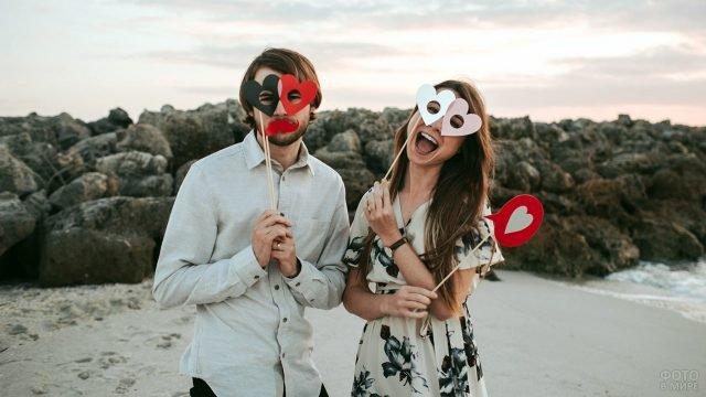 Парочка позирует с масками-валентинками на берегу моря