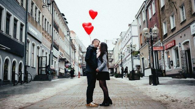 Парочка с шариками-сердечками целуются на европейской улочке