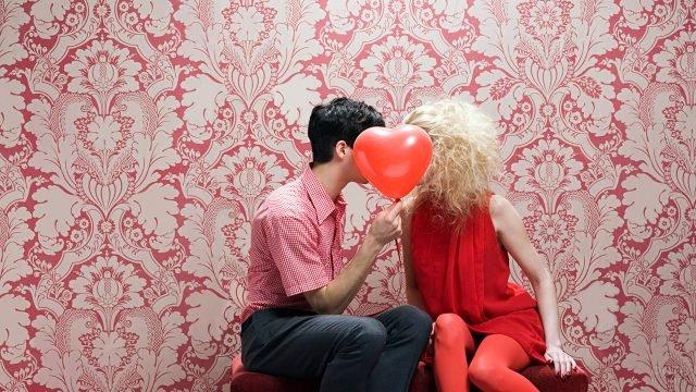 Парочка сидит на фоне гламурных обоев, пряча лица за шариком-сердечком