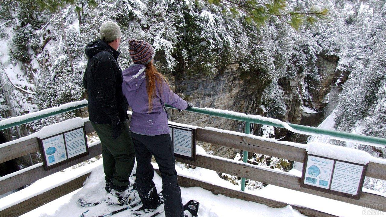 Парочка смотрит на зимнюю горную реку со смотровой площадки