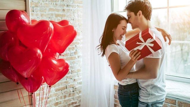 Счастливая девушка с подарком в объятьях любимого в светлой комнате с шариками-сердечками