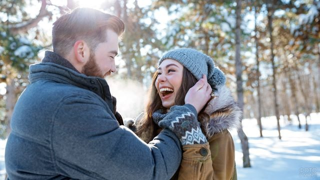 Смеющаяся молодая пара смотрят друг на друга в зимнем лесу