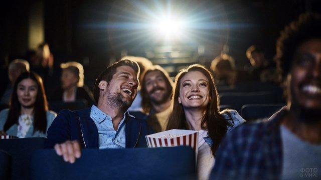Смеющаяся парочка смотрит фильм в кинотеатре