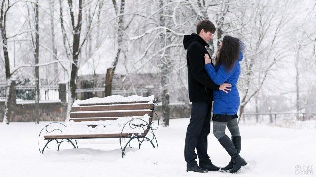 Влюблённая пара стоит в обнимку в зимнем парке