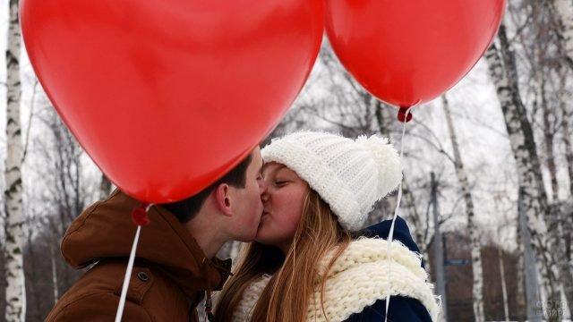 Влюблённая парочка целуются в зимнем парке под шариками-сердечками