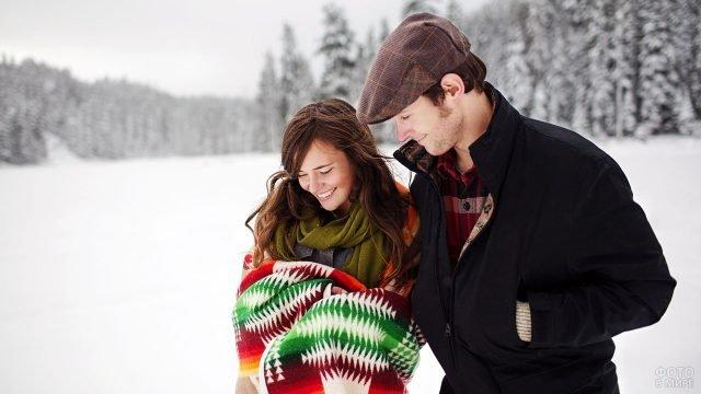 Влюблённая парочка прогуливается по опушке зимнего леса