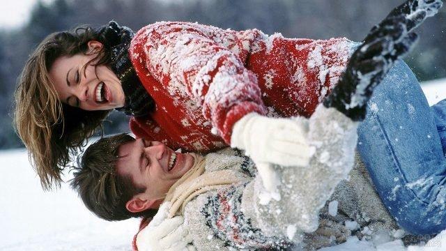 Влюблённые дурачатся в снегу на природе