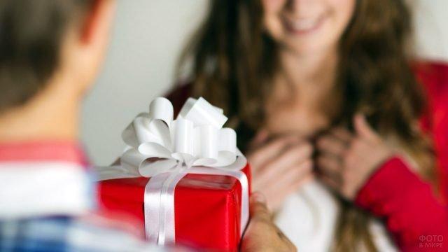 Вручение подарка в красной обёртке крупным планом