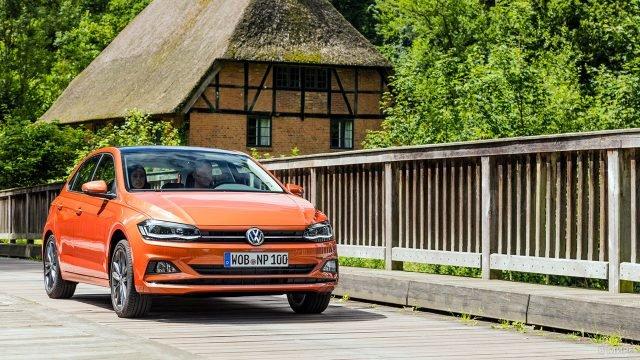 Парочка в оранжевом Фольксвагене Поло едет по деревянному мосту в туристическом местечке