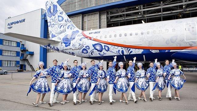 Народный ансамбль в национальных костюмах рядом с нарядным Аэробусом Аэрофлот у ангара