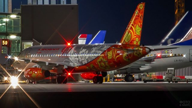 Самолёт в нарядной расцветке под хохлому компании Аэрофлот в вечернем аэропорту