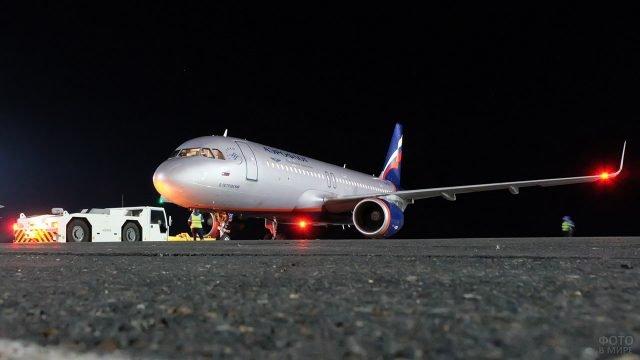 Техники работают с самолётом Аэрофлота на ночной взлётной полосе