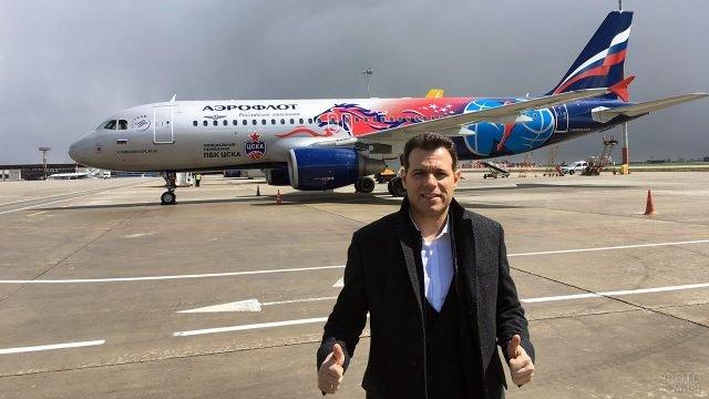 Журналист на фоне самолёта Аэрофлот в расцветке партнёра баскетбольного ЦСКА