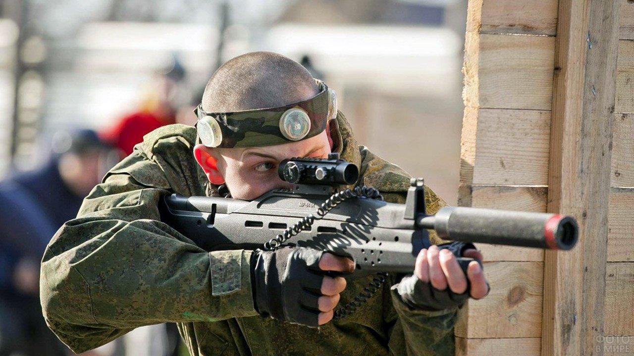 Участник военной реконструкции в честь 23 февраля позирует с оружием
