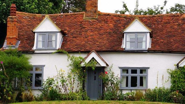 Фронтон белого сельского дома с мансардой под красной черепичной крышей