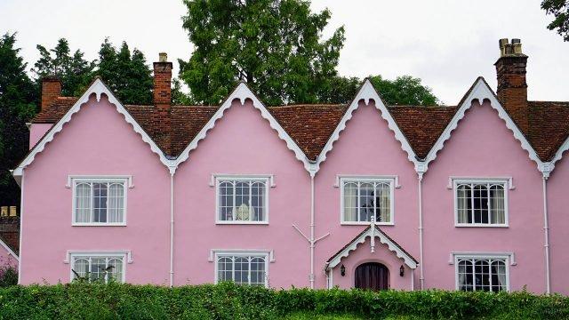 Розовый фасад дома под красной черепичной крышей с треугольными фронтонами